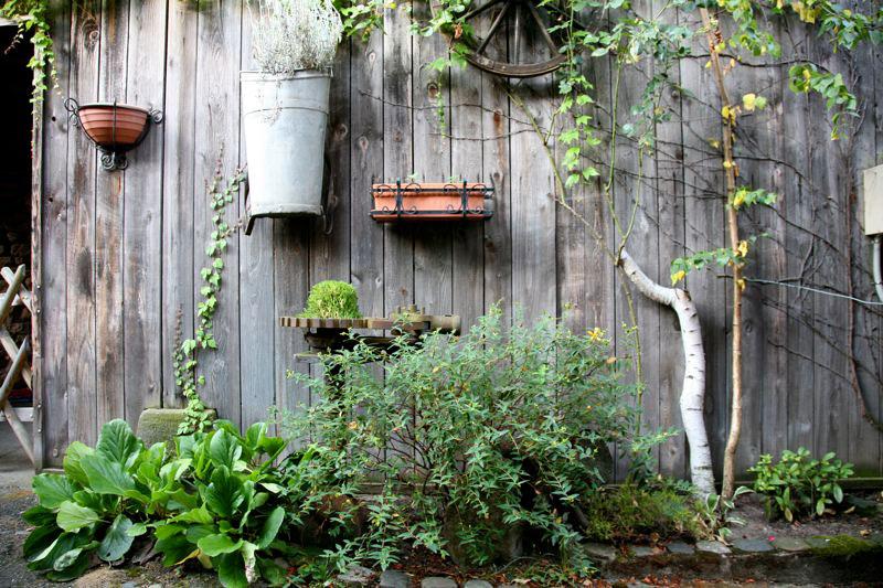 holzener-zaun-mit-blumen-und-pflanzen-einem-alten-rad-usw