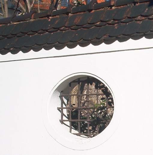 Geputzte Mauer mit Biberschwänzen und Fenstergitter