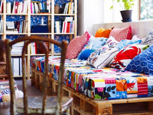 Paletten-Sofa mit Patchwork-bezogener Matratze und fröhlich bunten Kissen
