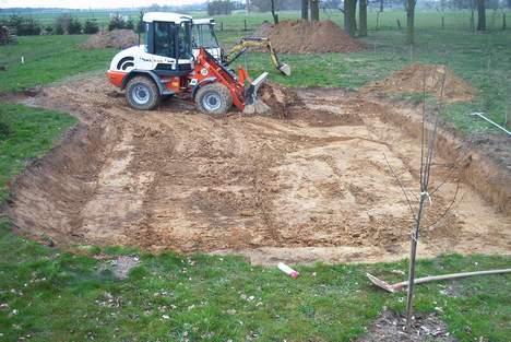 Der Radlader beseitigt die Grasnarbe und den Mutterbodenl
