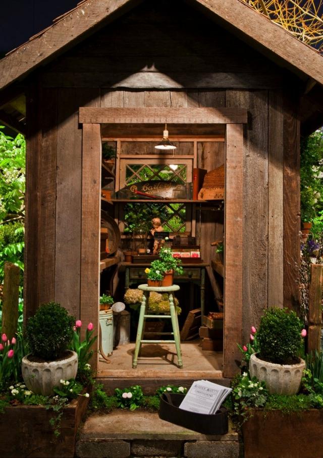 rustikales-Gartenhaus-Holz-Naturoptik-schöne-Wandregal-frische-Blumen