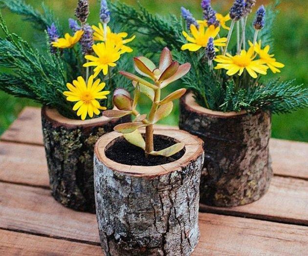 Blumen in Holzstammtöpfen